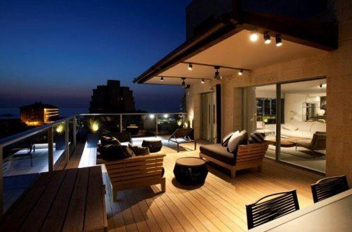 מרפסת גג מעוצבנת עם נוף לים לאור שקיעה