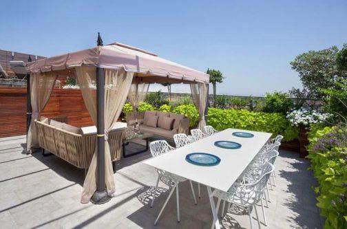 מרפסת גג מעוצבת עם פינת אוכל וגזיבו עם ספות
