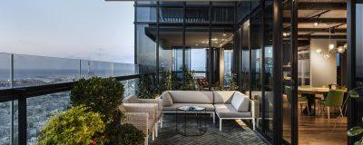 מרפסת פנטהוז מעוצבת עם צמחיה ופינות ישיבה