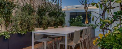 גינה במרפסת עם צמחיה מטפסת ופינת אוכל גדולה