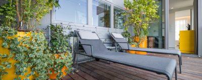 גינת גג בשילוב אדניות כתומות בהתאם לעיצוב הפנים עם עצים ושיחים מתפסים