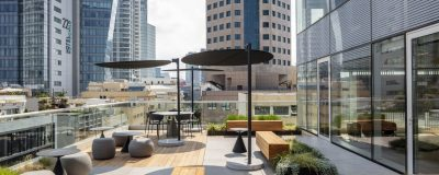 עיצוב מרפסת של בניין משרדים - פינות ישיבה, הצללה, וצמחים ירוקים